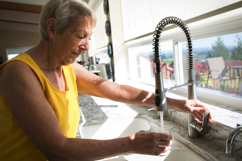 PMG PHOTO: JAIME VALDEZ - Betty Rose fills a cup of tap water at her home near Westside Rock Hayden Quarry, which has been fined for illegally storing industrial solid waste. She's worried the illegally stored materials are contaminating her well water.