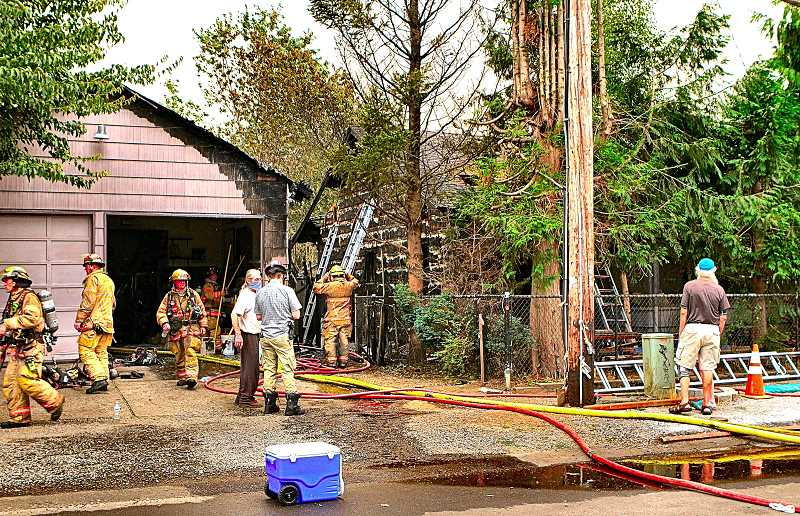 DAVID F. ASHTON - After knocking down the fire on the outside of the structure, crews worked inside the adjacent detached garage, making sure no embers remained.