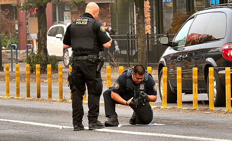 DAVID F. ASHTON - An officer watches, as a colleague examines a bullet casing left behind when the occupants of two cars fired shots at each other on S.E. 82nd at Powell Boulevard, while both were driving south.
