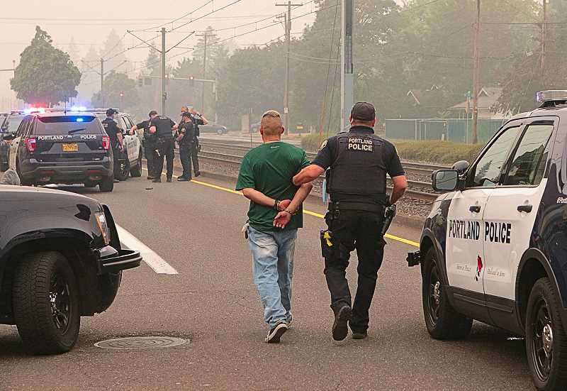 DAVID F. ASHTON - One of the two subjects involved in the September 10th incident in the Hazelwood neighborhood of East Portland was walked, in handcuffs, to the squad car dimly visible through the heavy wildfire smoke. The other subject was already in custody.