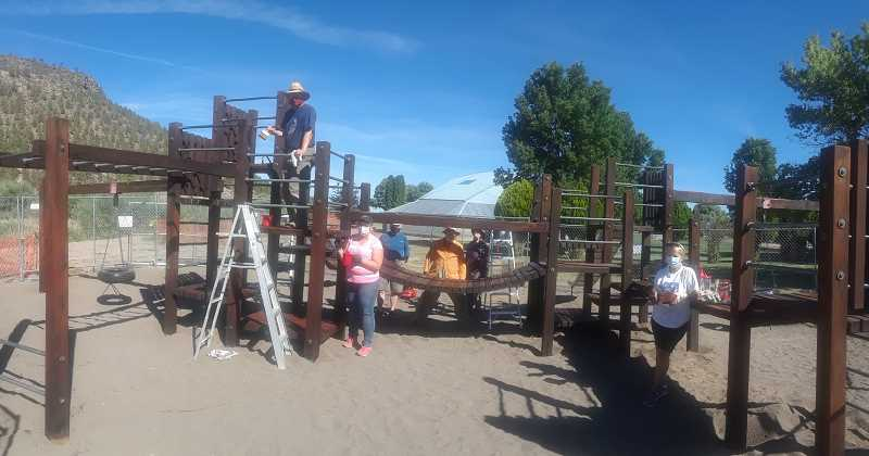 PHOTO COURTESY OF KIWANIS CLUB OF PRINEVILLE  - Kiwanians pose for a photo at the Kiwanis Children's Park play structure near the Les Schwab amphitheater. A group of five members prepped and restained the structure over the course of a few days.