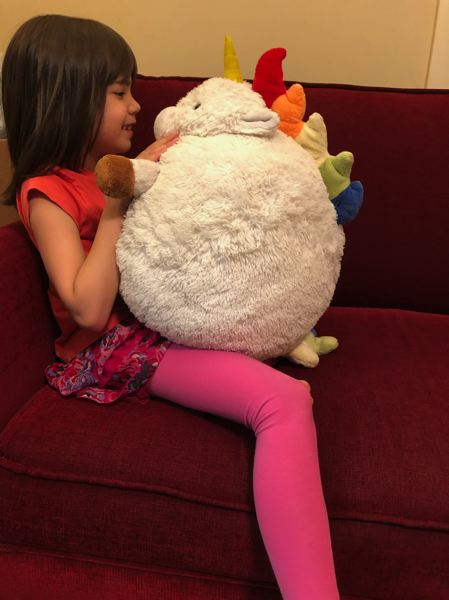 COURTESY PHOTO: ROBYN LIU - Mika, 7, hugs a toy unicorn named 'Skittles' given to her to watch over by an elementary school counselor. Mika's family had to evacuate their home as the neighbor's house caught fire.