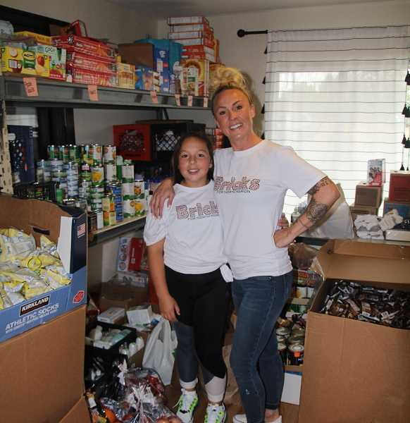 PMG PHOTO: JUSTIN MUCH - Woodburn-area Community Hero Whitney Workman, right, and her daughter, Kinzee, after bringing in supplies on Sept. 23 at the pantry serving 'Bricks for North Marion,' a non-profit she created this year.