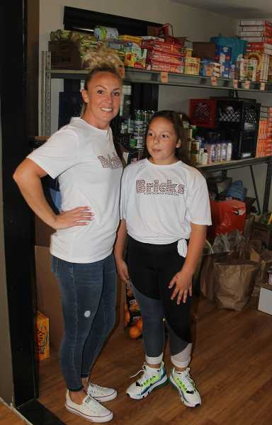 PMG PHOTO: JUSTIN MUCH - Woodburn-area Community Hero Whitney Workman, left, and her daughter, Kinzee, after bringing in supplies on Sept. 23 at the pantry serving 'Bricks for North Marion,' a non-profit she created this year.