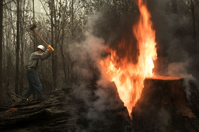 PMG PHOTO: JAIME VALDEZ -  Loren Good, a member of the Mennonite Church, cuts down trees near a fire burning a snag on Paul Clement's property.