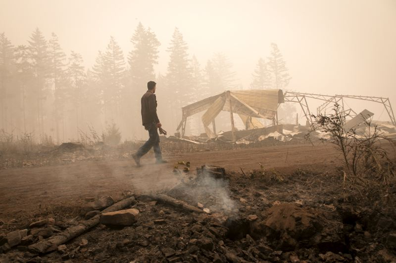 PMG PHOTO: JAIME VALDEZ - Paul Clement walks along an area that burned near his property.