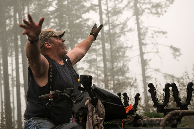 PMG PHOTO: JAIME VALDEZ - John Hil raises his arms towards the trees behind his home and describes how the sky was a bright red glow from the fire that somehow missed his family's home in Estacada.