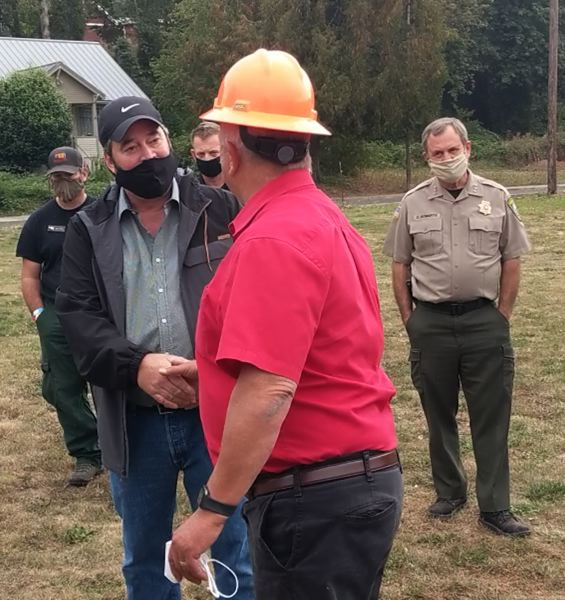 PMG PHOTO: EMILY LINDSTRAND - Clackamas County Commissioner Jim Bernard shakes hands with Estacada Mayor Sean Drinkwine while discussing the Riverside and Dowty Road fires.