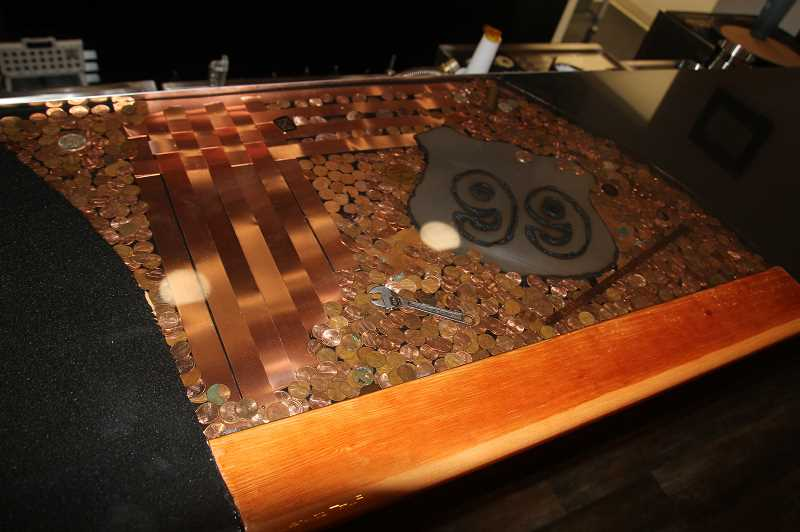 PMG PHOTO: JUSTIN MUCH - Old coins and artifacts from the Brooks area adorn the glossy top bar at Route 99, which opened in late August.