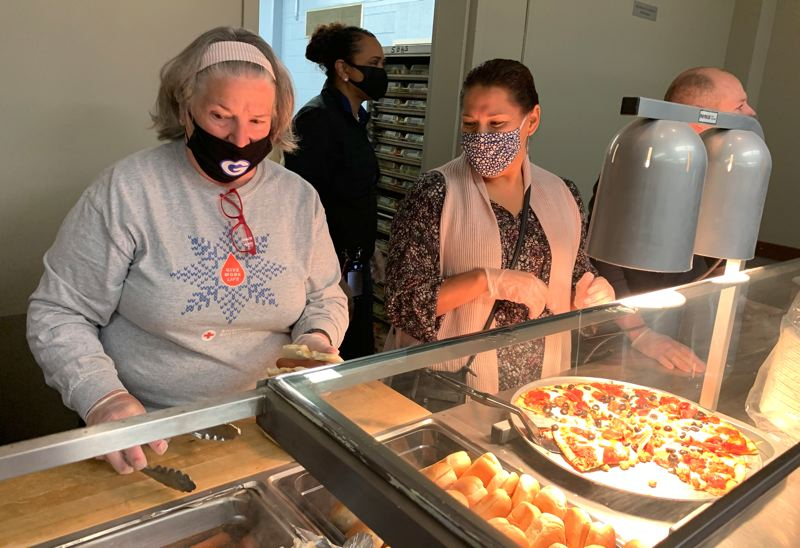 COURTESY PHOTO: GRESHAM-BARLOW SCHOOL DISTRICT - Gresham-Barlow school board members and superintendent feed the firefighting staff camped at Barlow High School before the command center catering trucks were fully functional. Sodexo Group, which runs the school cafeteria, donated the food.