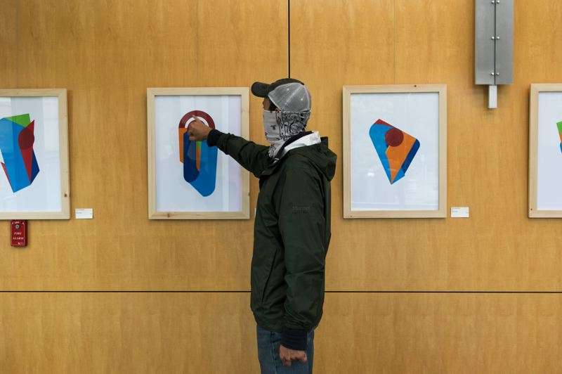 PMG PHOTO: JAIME VALDEZ - Pacific University professor Tyler Brumfield points at a graphic image piece at his new exhibit 'Everyday Abstractions' at the Hillsboro Civic Center.