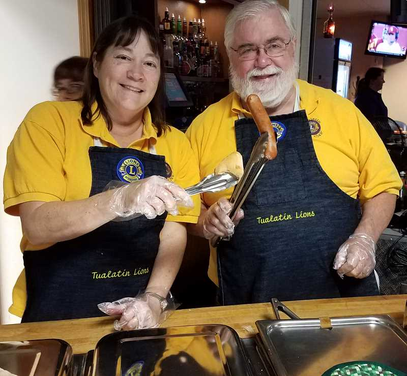 COURTESY PHOTO: TUALATIN LIONS CLUB - Tualatin Lions Jackie Dannemiller and Ed Casey display the famed Zenner-brand German sausages that make the annual Tulatin Lions Oktoberfest such a hit.