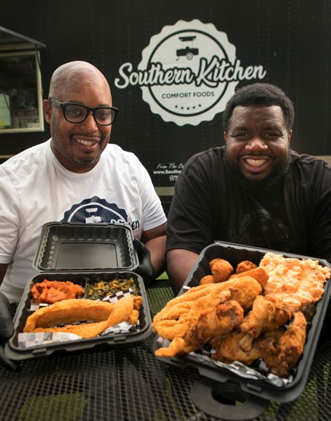 JAIME VALDEZ/PMG - Southern Kitchen PDX owners Jermaine Atherton, left, and Maurice Fain show a couple dishes of comfort food they make such as fried catfish and chicken at their food cart along North Mississippi Avenue