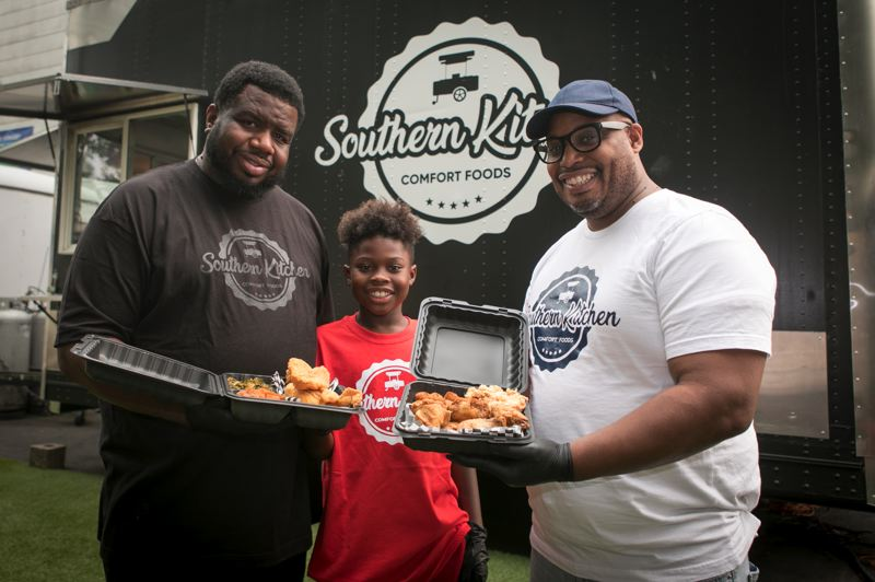 JAIME VALDEZ/PMG - (From left): Maurice Fain; his son, Zaire,10; and Jermaine Atherton stand by their Portland food cart, Southern Kitchen PDX.