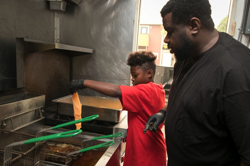 JAIME VALDEZ/PMG - Southern Kitchen PDX co-owner Maurice Fain watches his son Zaire,10, place a fillet of catfish into the fryer.