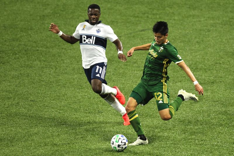 PMG PHOTO: JAIME VALDEZ - Portland Timbers left back Marco Farfan (32) plays the ball forward Sunday under pressure from Vancouver's Cristian Dajome.