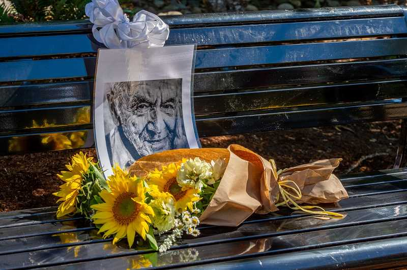 PMG PHOTO: DIEGO DIAZ - Flowers and a drawing of Alter Wiener lie on the bench dedicated to him Sunday in Sherwoods Synder Park.