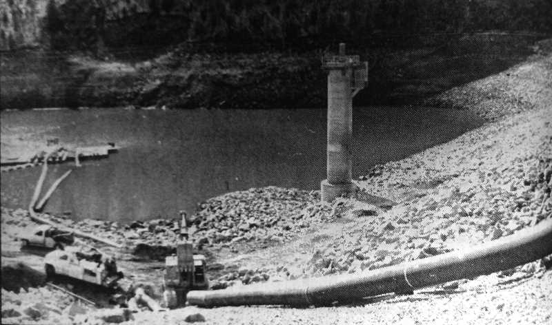 CENTRAL OREGONIAN - October 3, 1995: Pumps, booster pumps and pipes are being installed at Ochoco Reservoir to keep the water flowing, draining the reservoir level to a point that excavation on the sinkhole can begin.