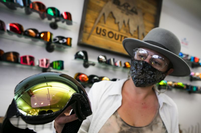 PHOTO BY JAIME VALDEZ - Amber Sinz, a buyer and manager at U.S. Outdoor Store, holds a pair of Dragon ski goggles available for sale at the store.