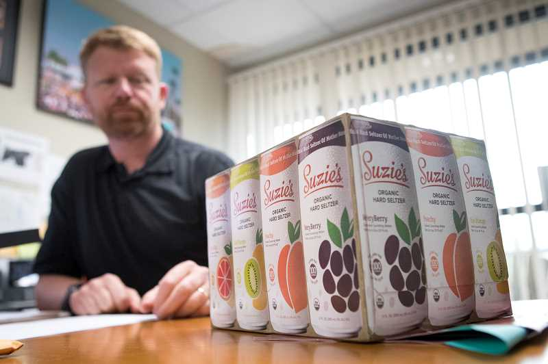 PMG PHOTO: JAIME VALDEZ - Chris Barhyte, CEO of Suzies Organics, displays a 12-pack of the hard seltzer his company rolled out on Aug. 1. Although the product is made at the companys headquarters in Pendleton, Suzies Organics has its administrative offices in Tualatin.