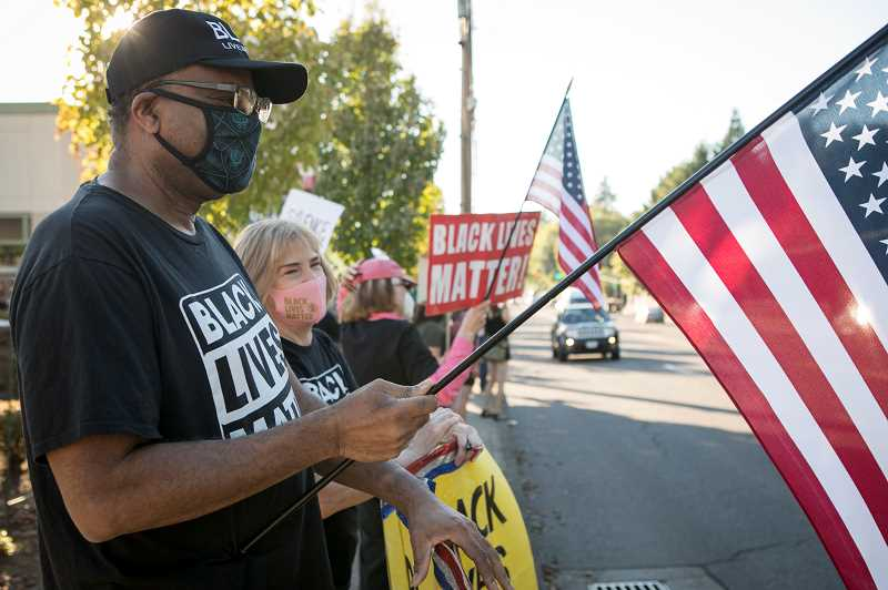 PMG PHOTO: JAIME VALDEZ - Reginald Liggins and wife, Julie, participate in a Black Lives Matter vigil along Beaverton-Hillsdale Highway.
