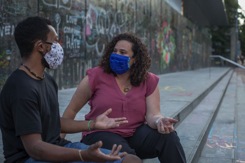 COURTESY  - Rima Ghandour speaks with a potential constituent near a Black Lives Matter mural in Portland.