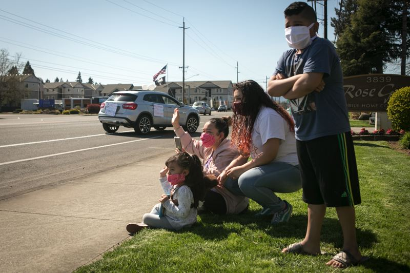 PMG PHOTO: JAIME VALDEZ - A family in Cornelius watches a local parade. The columnist, a health care worker, explains why wearing a mask makes sense for him.