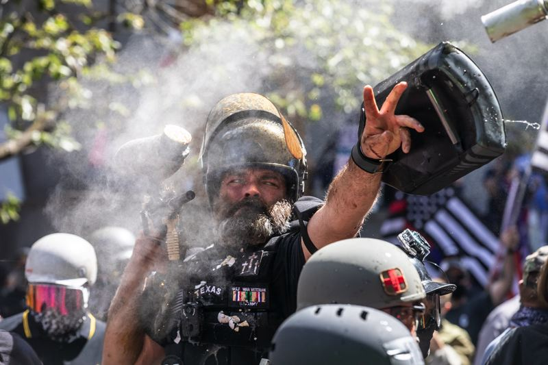 PMG PHOTO: JONATHAN HOUSE - Alan Swinney lobs a smoke bomb while holding a paint ball gun during a violent clash between protesters on Saturday, Aug. 22 in Portland. Swinney was later captured on video pointing a revolver at the crowd.