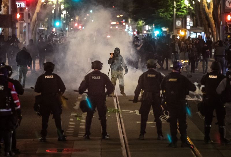 PMG PHOTO: JONATHAN HOUSE - Protesters squared off with Portland Police Bureau officers dressed in riot gear during a demonstration that began Sunday, June 7.