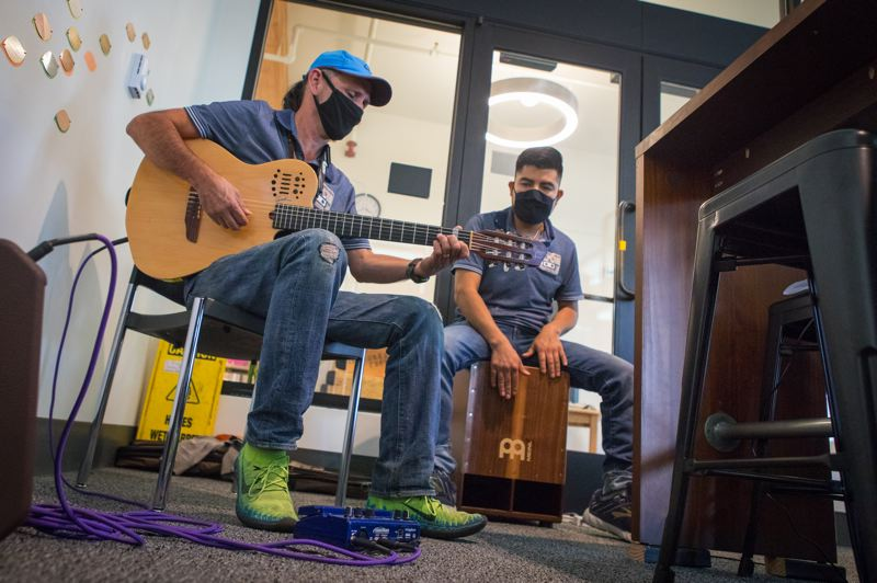 PMG PHOTO: JAIME VALDEZ - Alex Contreras plays guitar while Juan Ruiz drums along at Universal Coffee. The two musicians own the mobile coffee bar located in the Cornelius Public Library.