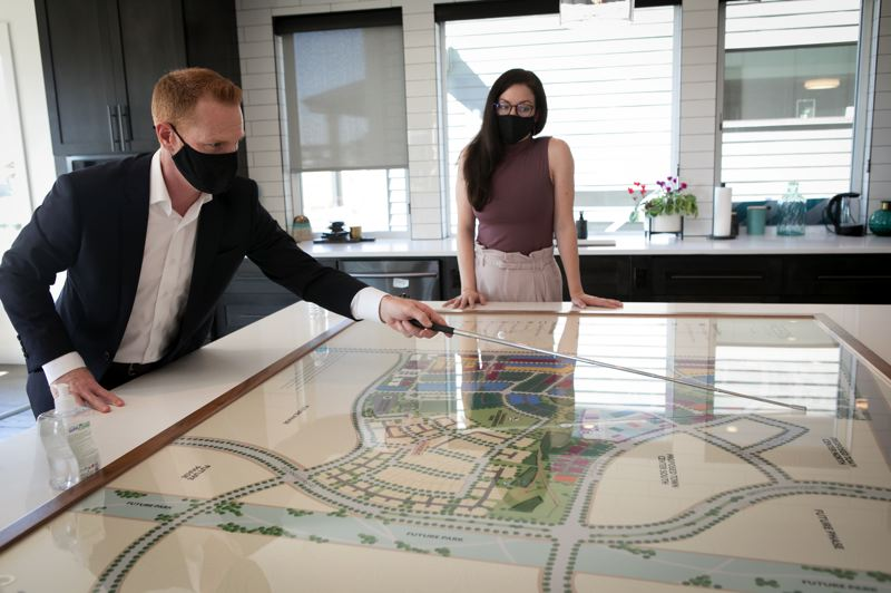 PMG PHOTO: JAIME VALDEZ - Eric Peterson and Allyse Paetsch of developer Newland Communities explore the latest iteration of the Reeds Crossing map, showing how five home builders are being spread across the huge property.
