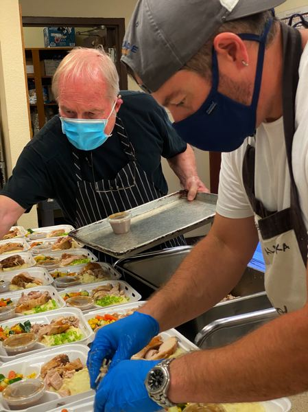 COURTESY PHOTO - Chef Dominic Sachet, foreground, and volunteer Ken Brooks, background, ready boxed salads for delivery at the Marjorie Stewart Senior Community Center in Sherwood.