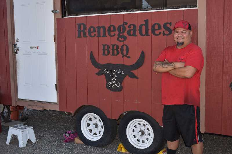 RAMONA MCCALLISTER - David Brown stands proudly in front of Renegades BBQ food cart, where he and co-owner Jerry Roland serve a wood-smoked BBQ menu. The two owners opened on May 30 at the food court on Northeast Third Street.