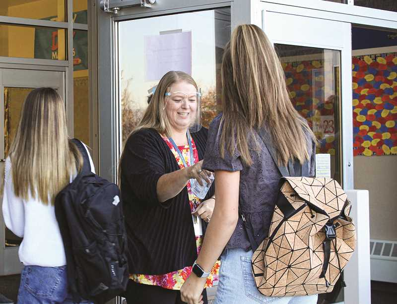 FRANCES CHANEY - Patty Bates, youth transition specialist, gives Crook County High School students hand sanitizer as they enter the school Monday morning.
