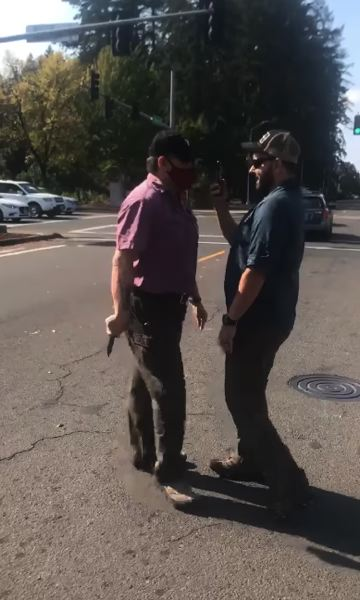 COURTESY: JANIRA BRANNIGAN - A man with a knife confronts a rallygoer with a cellphone at an Oregon Women for Trump car caravan in Hillsboro on Sunday.