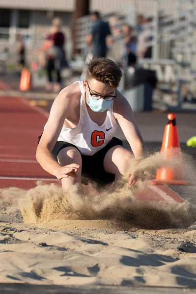 LON AUSTIN  - Trent Reese lands a long jump in Culver's track meet against Crook County.