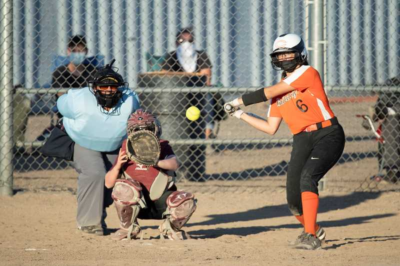 LON AUSTIN  - Hensley Watcher belts one of her two first-inning home runs against Redmond.