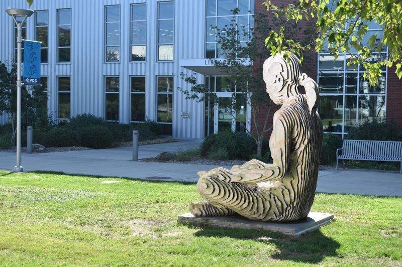 PMG PHOTO: TERESA CARSON - This 'student' was the only one around on Portland Community College's Southeast Campus on a recent afternoon. She is 'The Reader' by Julian Voss-Andreae.