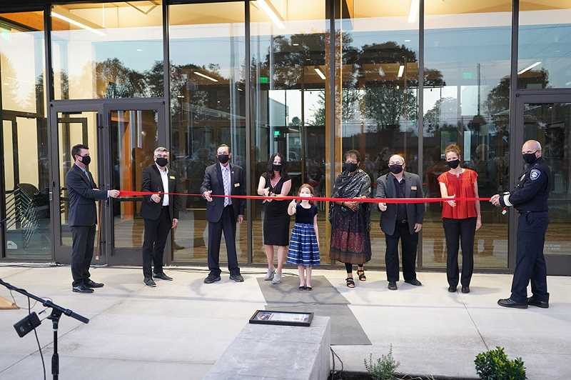 COURTESY PHOTO - Oregon City Officer Robert Libke's widow and daughter, Wendy and Ziva Libke (middle), joined members of the city commission, the city manager and police chief in cutting the ribbon on the new OCPD headquarters.