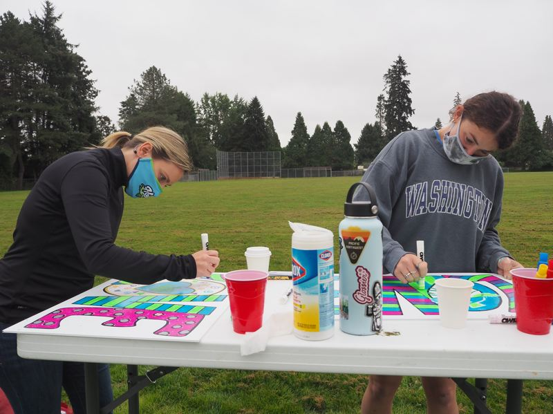PMG PHOTO: MAX EGENER - Jen Anderson, left, senior director of fan experience with the Hillsboro Hops, and Hallie Holton, an account executive, create colorful signs as part of LOVE on the FENCE.