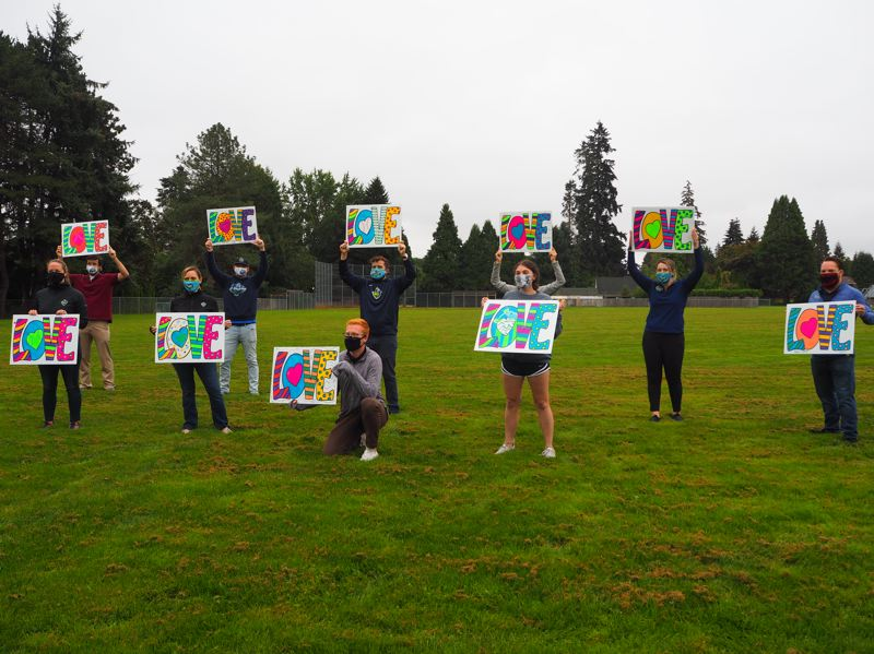 PMG PHOTO: MAX EGENER - Staff with the Hillsboro Hops hold up their 'LOVE' signs at the Peter Boscow Conference Center as part of the LOVE on the FENCE project by AgeCelebration.