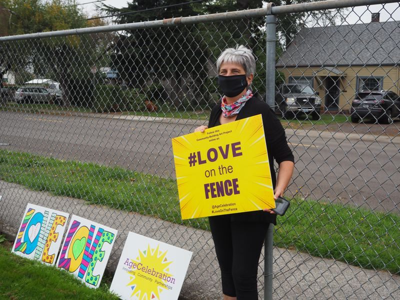 PMG PHOTO: MAX EGENER - Cindy Cosenzo, director of AgeCelebration, a consulting business in Hillsboro, promotes her project, LOVE on the FENCE, which brings together local nonprofits to create colorful signs and place them on fences throughout the community.