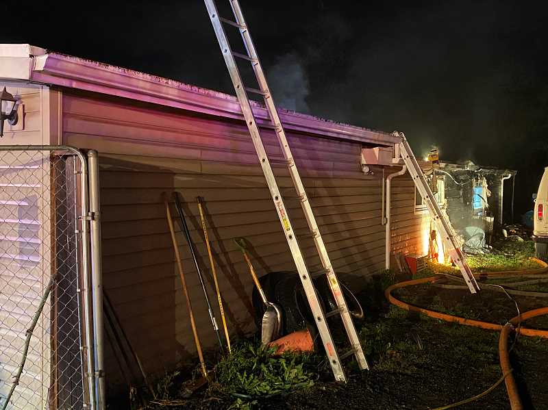 COURTESY PHOTO: TUALATIN VALLEY FIRE & RESCUE  - According to Tualatin Valley Fire & Rescue, first incoming crews found heavy smoke and flames coming from the exterior of the home behind the garage.