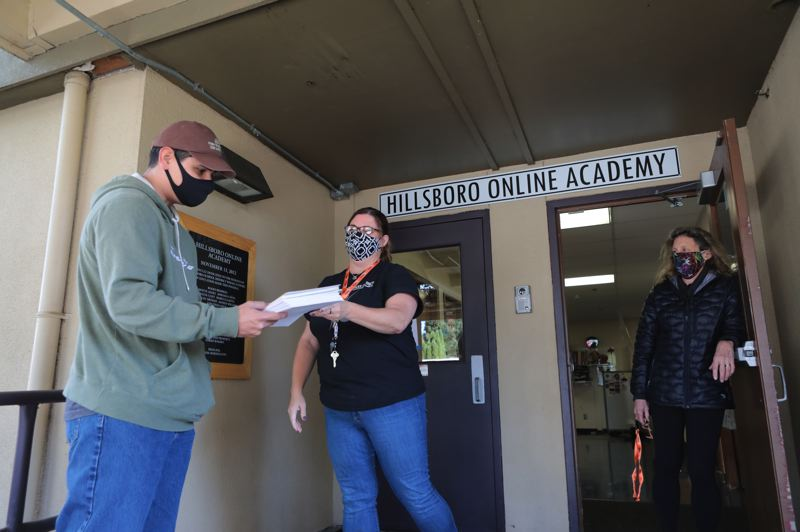 PMG PHOTO: JAIME VALDEZ - Corey Mackura picks up a packet for his first grade son from Shannon Freudenthal, dean of students at Hillsboro Online Academy, as Principal Linda Harrington watches at the Peter Boscow Conference Center.