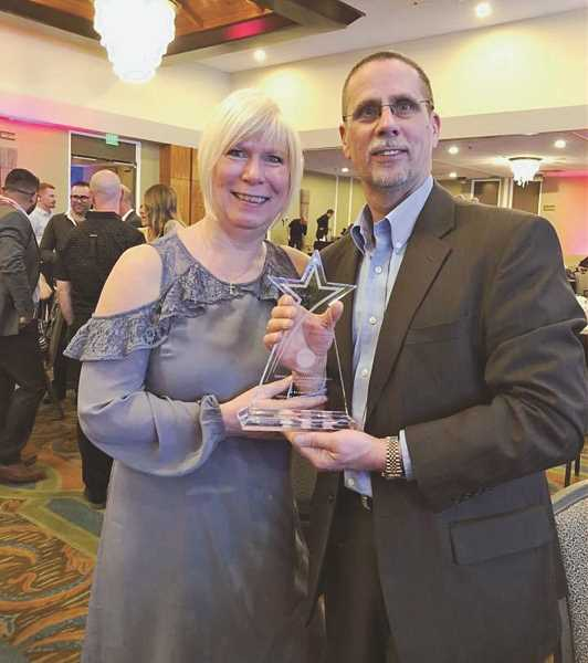 COURTESY PHOTO - Rhonda (left) and Lambert Bourgo pause for a photo upon winning a corporate award from Grocery Outlet in 2018.