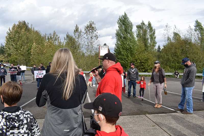 PMG PHOTO: RAYMOND RENDLEMAN - George and Valerie Lee, board members of Oregon City Youth Sports, speak at the Oct. 10 rally to reopen school facilities for activities.