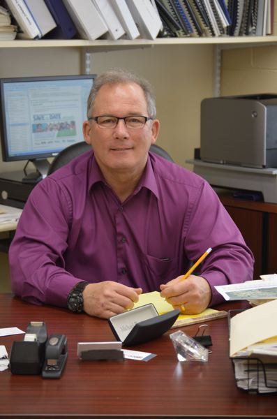 PMG PHOTO: COURTNEY VAUGHN - Michael Sykes, pictured at his desk in Scappoose City Hall in 2015, was recently honored by the League of Oregon Cities for his years of service as city manager in Forest Grove and Scappoose.