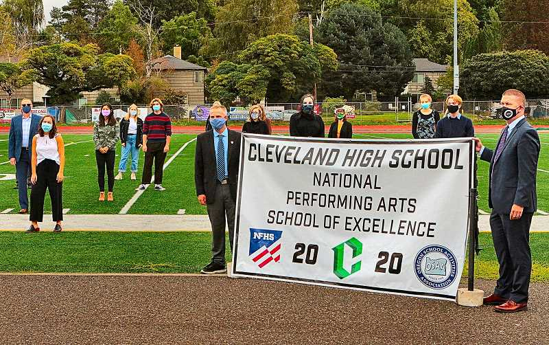 DAVID F. ASHTON - At the CHS athletic field, officials from the National Federation of State High School Associations present the banner proclaiming Cleveland High School this years national 2020 NFHS Performing Arts School of Excellence.