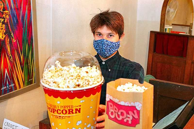 DAVID F. ASHTON - Although hes not yet back to showing motion pictures, Moreland Theater employee Noah Wass is happy to say hello to supportive patrons, and to sell large tubs of freshly-popped popcorn in the lobby.
