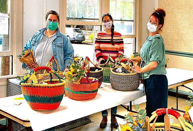 DAVID F. ASHTON - Putting finishing touches on some outgoing Sellwood Community House Harvest Baskets before they are to be delivered are, from left, Program Managers Ashley Asbjornsen, Elizabeth Milner, and Erin Fryer.